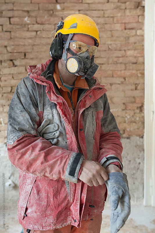 Construction worker puts on gloves. by Jelena Jojic Tomic for Stocksy United