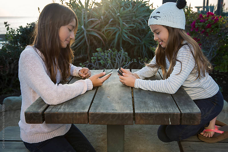 Girls sending text using a mobile phone by Curtis Kim for Stocksy United