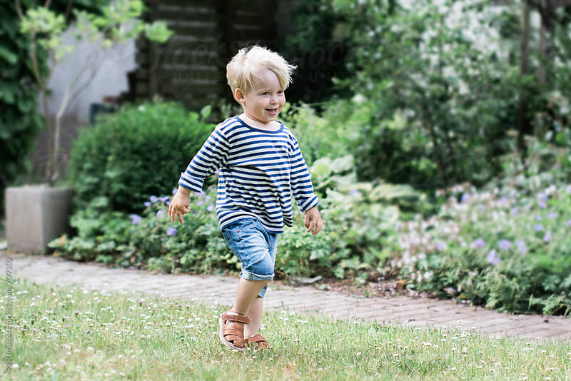 3 year old happy boy walking in a garden by Per Swantesson for Stocksy United