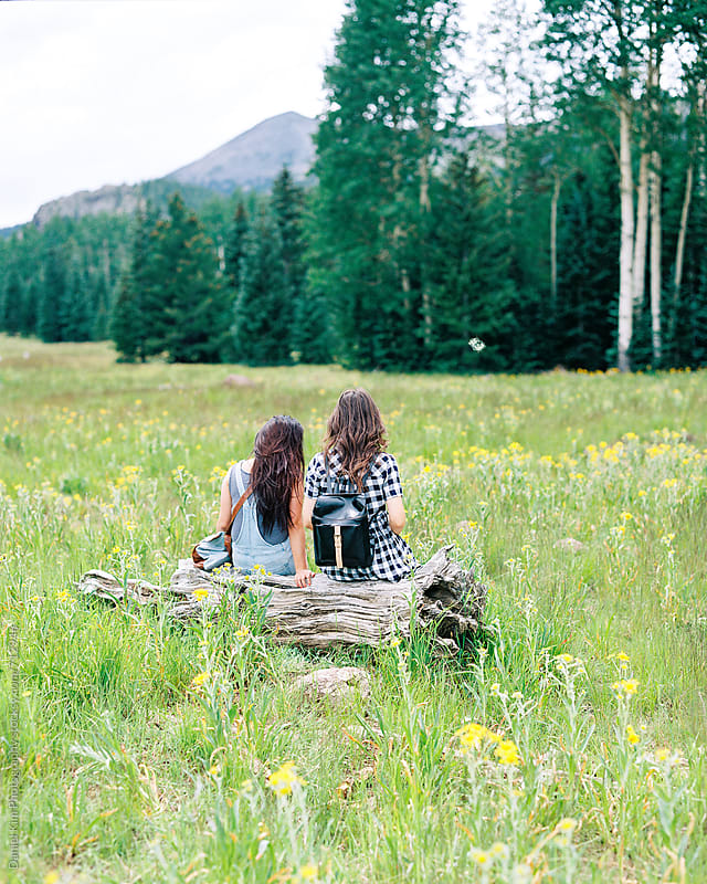 Two friends sitting in meadow by Daniel Kim Photography for Stocksy United