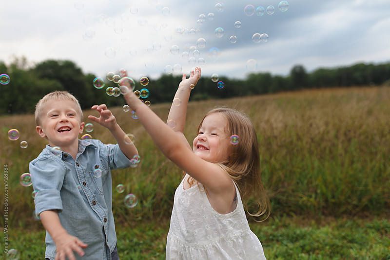Brother and sister pop bubbles, happy by Amanda Worrall for Stocksy United