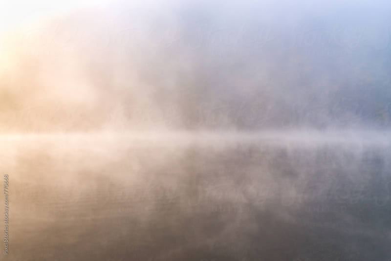 Lake covered in dense fog in the morning by Pixel Stories for Stocksy United