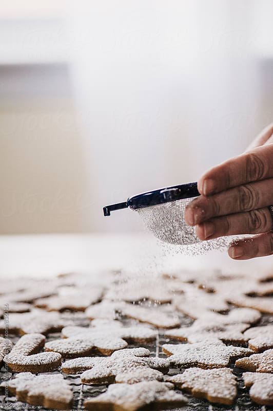 Sifting powdered sugar onto Gingerbread cookies by Cameron Whitman for Stocksy United