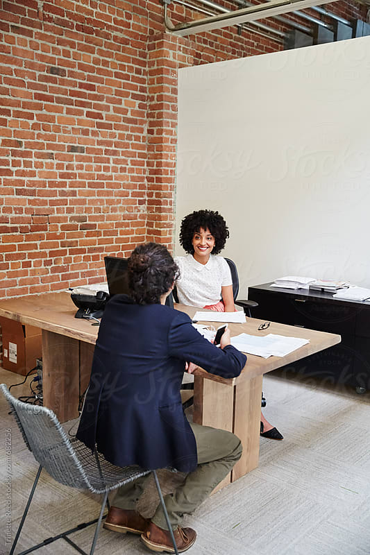 Woman interviewing man for a job in office by Trinette Reed for Stocksy United
