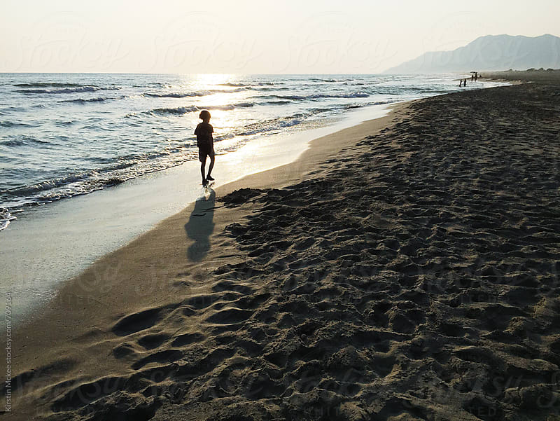 Silhouette of boy walking along Patara Beach by Kirstin Mckee for Stocksy United