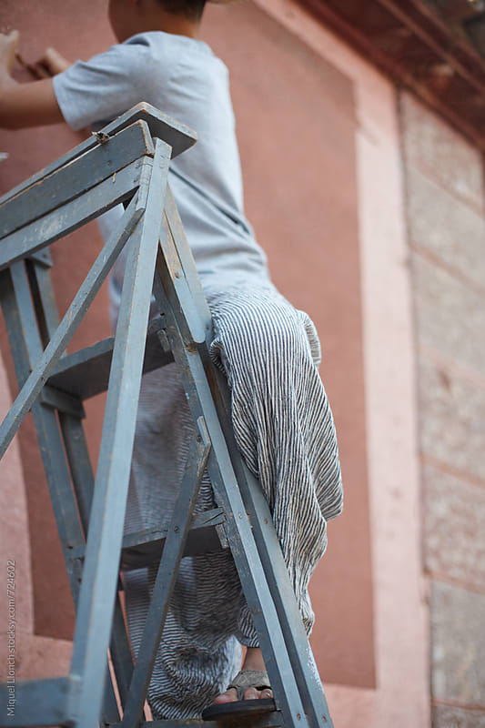 Close up of a young boy working on a ladder by Miquel Llonch for Stocksy United