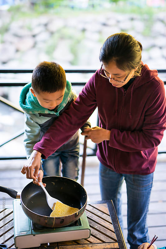 Adult holding kid's hand cooking French toast by Lawren Lu for Stocksy United
