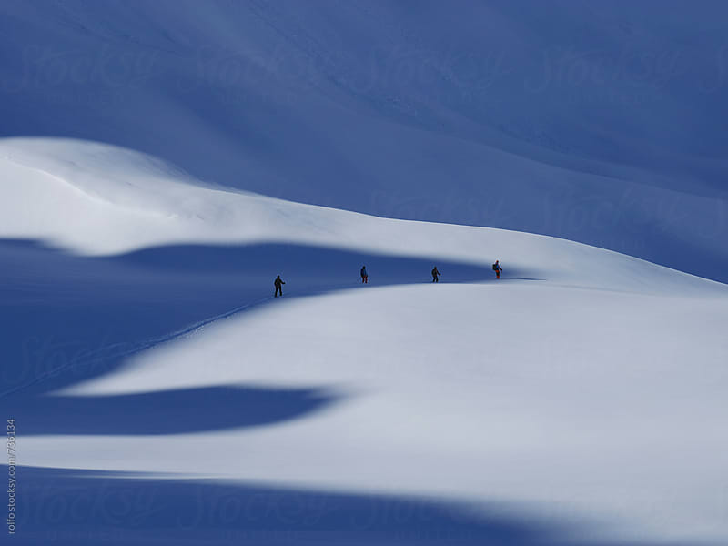 group of skiers in snowy mountains by rolfo for Stocksy United