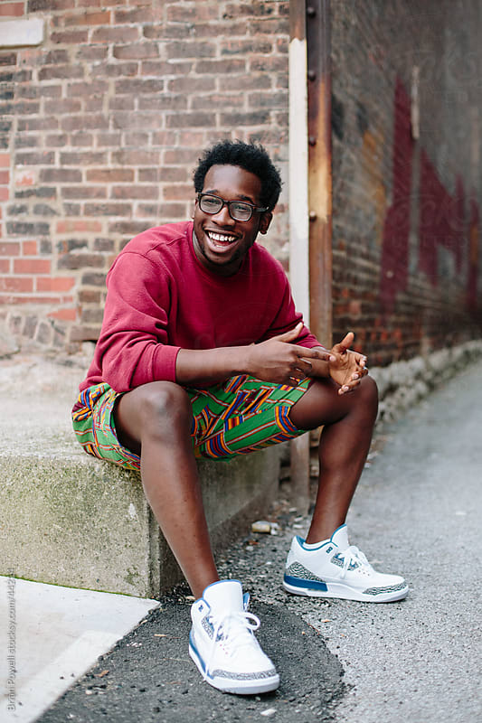 young Black man wearing glasses.  by Brian Powell for Stocksy United
