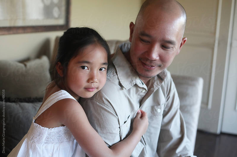 Asian daughter hugging father while making direct eye contact with camera  by Dina Giangregorio for Stocksy United