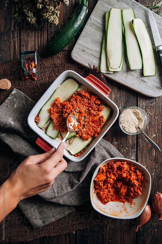 Woman making a lasagna with zucchini by Nataša Mandić for Stocksy United