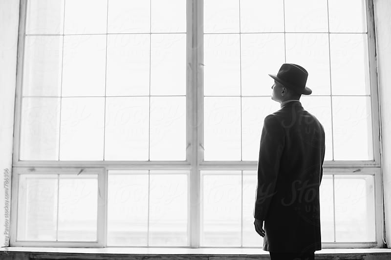 Man dressed in coat and hat standing in front of window by Andrey Pavlov for Stocksy United