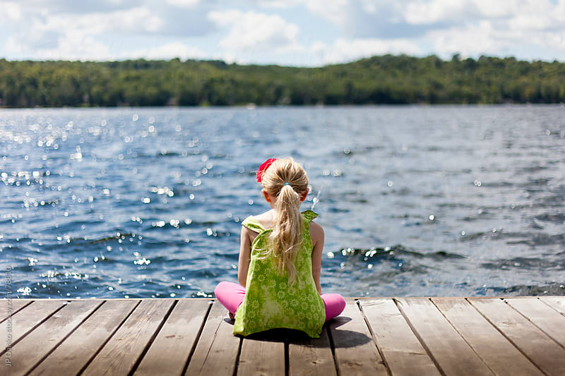 Little Girl Sitting on Dock At Cottage Lake by JP Danko for Stocksy United