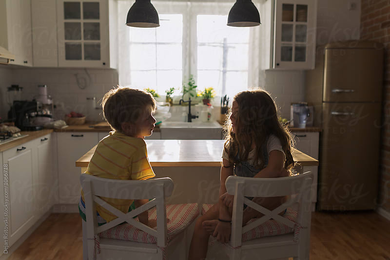 Siblings talking at home. by Dejan Ristovski for Stocksy United