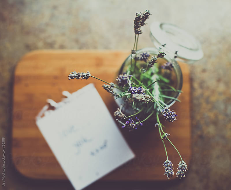 fresh lavender in glass container on wooden board with hand written paper saying love you by Lisa MacIntosh for Stocksy United