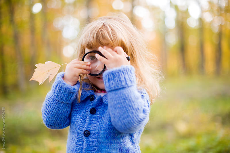 Little girl with a hand magnifier by Sveta SH for Stocksy United