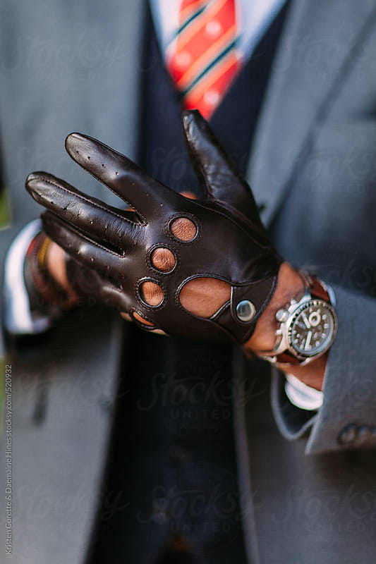 Close up of a man putting on perforated leather driving gloves by Kristen Curette Hines for Stocksy United