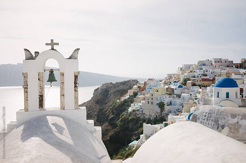 View of Oia over church with bells in Santorini by Kirstin Mckee for Stocksy United