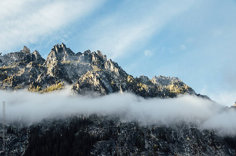 Jagged peaks rising above stripe of fog by Tari Gunstone for Stocksy United