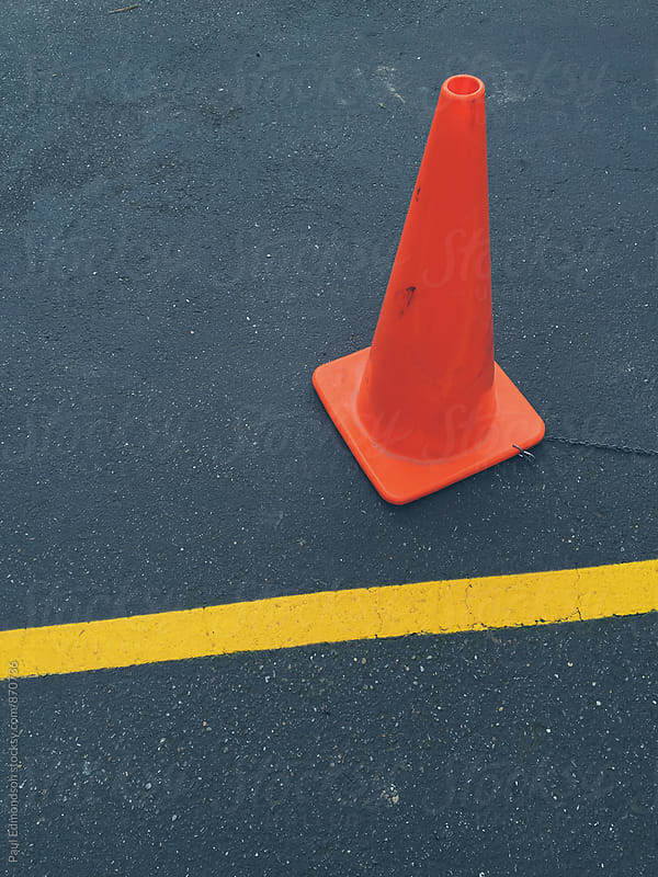 Traffic cone and yellow boundary line on road by Paul Edmondson for Stocksy United