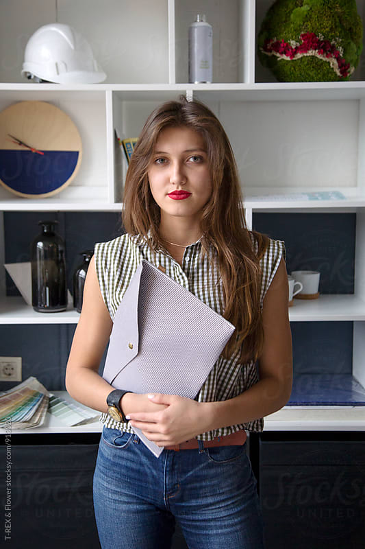 Attractive young woman holding folder by Danil Nevsky for Stocksy United