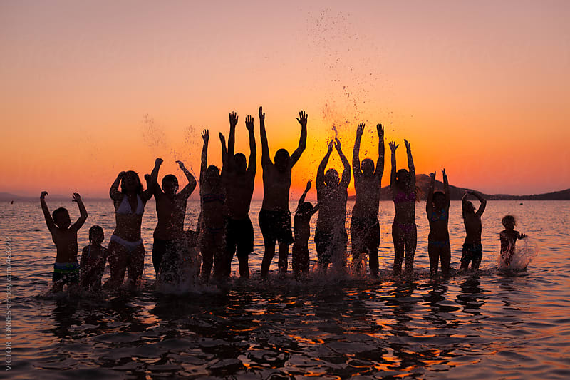 Big Family Jumping in the Sea at Sunset by VICTOR TORRES for Stocksy United