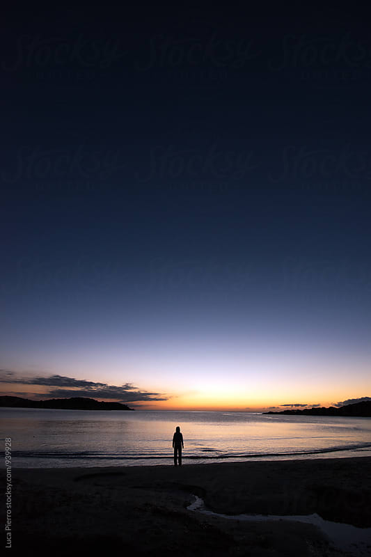 Woman standing on a beach looking the rising sun by Luca Pierro for Stocksy United