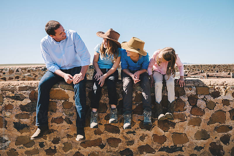 father with his daughters, sitting on a wall by Gillian Vann for Stocksy United