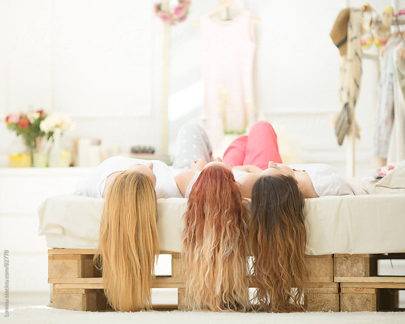 Three Teenage Girls Lying on Bed by Lumina for Stocksy United