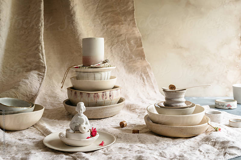 Close-up of handmade ceramic collection bowls, plates and cups. Asian statuette by Trent Lanz for Stocksy United