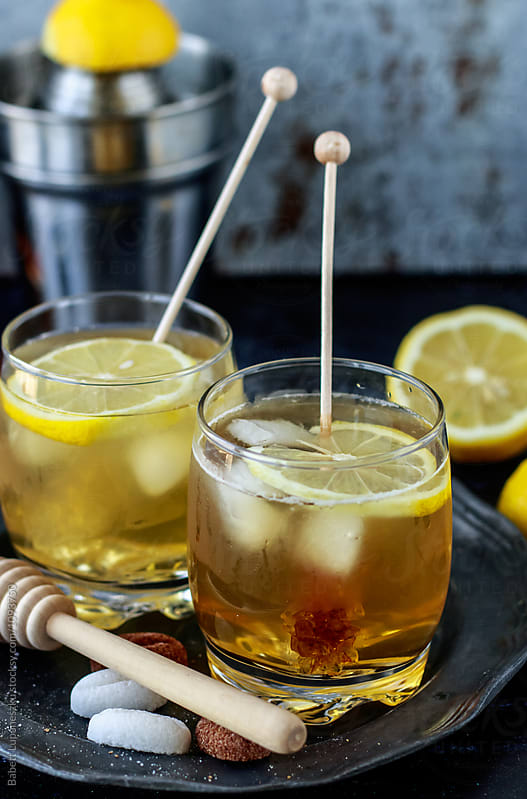 Bourbon  coctails with lemon and honey by Babett Lupaneszku for Stocksy United