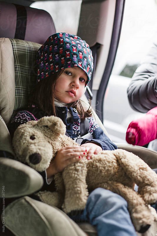A young girl is strapped into a car seat by her mother. by Holly Clark for Stocksy United