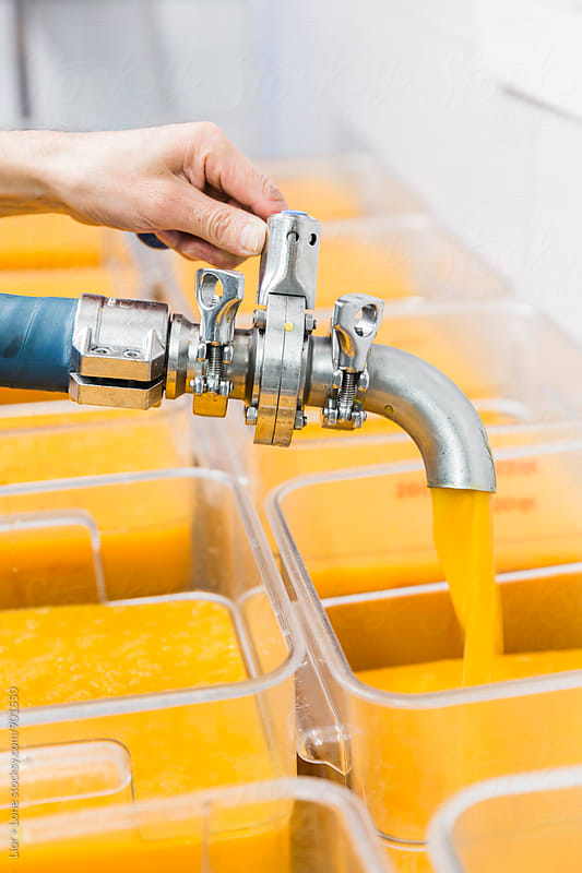 Hand holding industrial hose filling large containers with orange liquid by Lior + Lone for Stocksy United