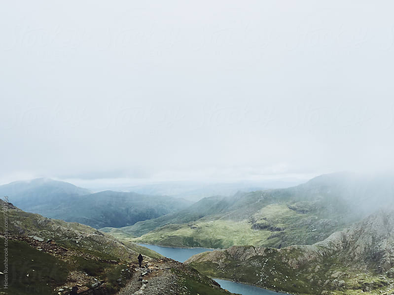 Misty Welsh mountains and a lone hiker by Helen Rushbrook for Stocksy United