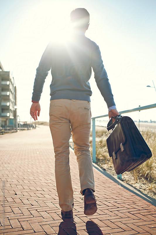 Happy business man walks home by Denni Van Huis for Stocksy United