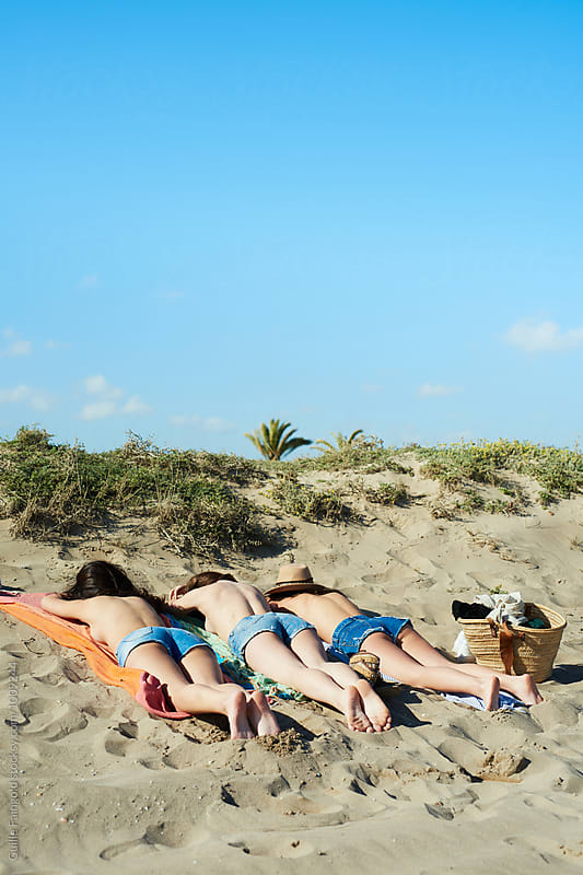 Back view of girls on beach getting tanned by Guille Faingold for Stocksy United