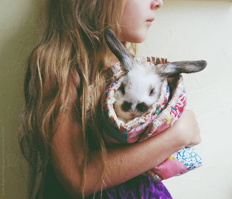 young girl holding pet bunny in blanket by Kristin Rogers Photography for Stocksy United