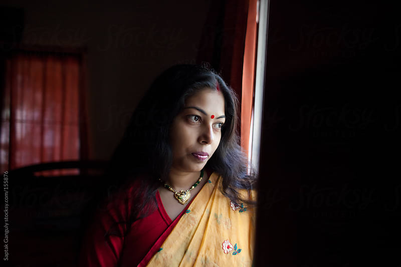 Beautiful young woman standing by the window by Saptak Ganguly for Stocksy United