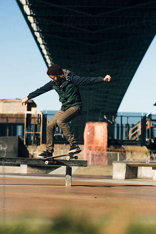 Skateboarder under bridge by Isaiah & Taylor Photography for Stocksy United
