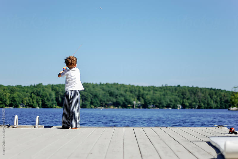 Boy fishes in a lake from a dock on a summer morning by Cara Dolan for Stocksy United