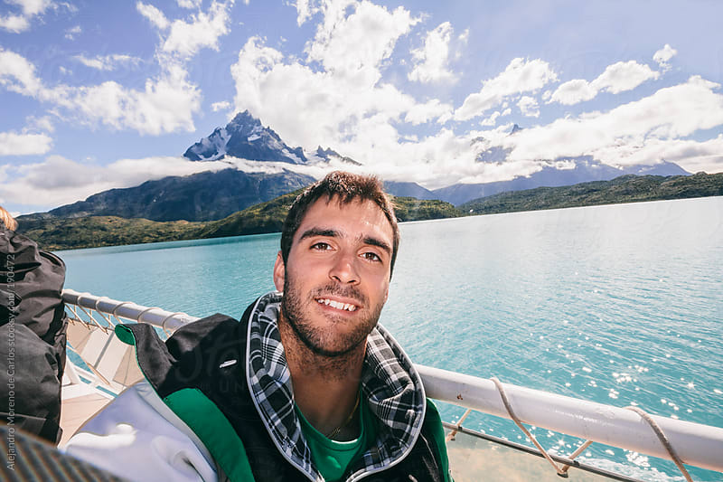 Young smiling man selfie on mountain and lake landscape while adventure travel in Patagonia by Alejandro Moreno de Carlos for Stocksy United