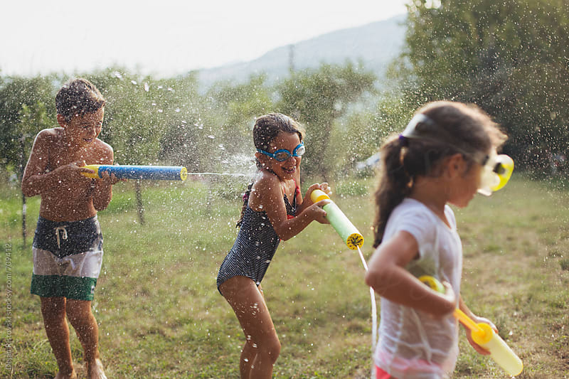 Children splashing with water by Dejan Ristovski for Stocksy United