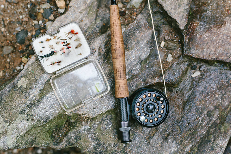 Fly fishing rod, reel and flies on river bank by Matthew Spaulding for Stocksy United