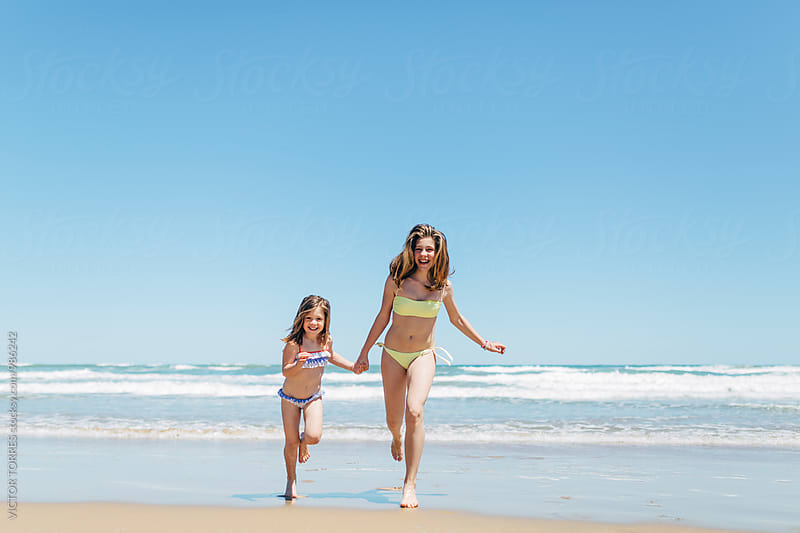 Little Sisters Running at the Beach by Victor Torres for Stocksy United