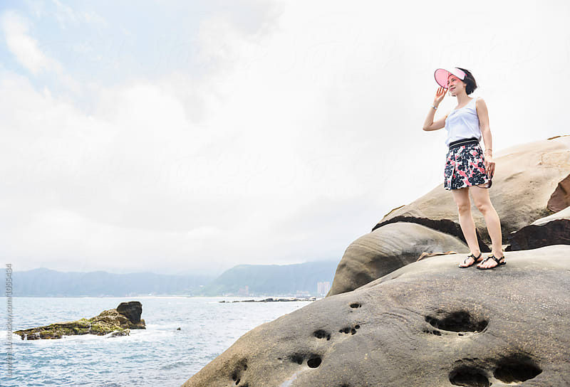 Adult woman on rock looking away by Lawren Lu for Stocksy United
