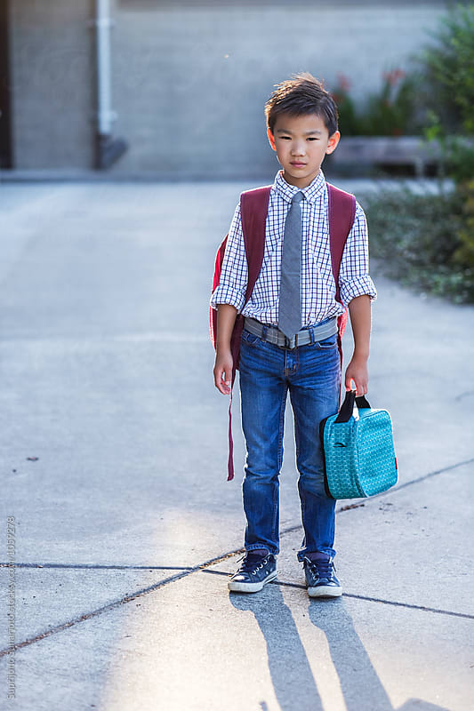 Back to school: Asian kid carrying a lunch bag in school by Suprijono Suharjoto for Stocksy United