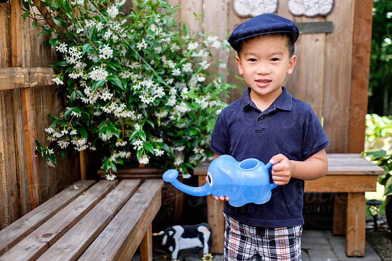 Asian kid holding a watering can in the backyard by Suprijono Suharjoto for Stocksy United