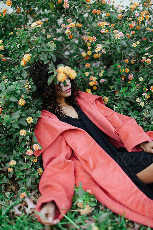 Woman laying in a flower bush by Kayla Snell for Stocksy United