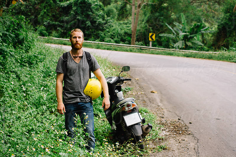young male stands in front of moto next to road by Jesse Morrow for Stocksy United