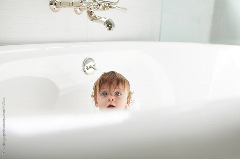 Baby In Oversized White Bathtub Peeking Over Edge by Dina Giangregorio for Stocksy United